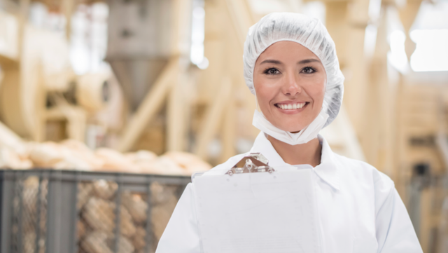 Woman in a hair net smiling.