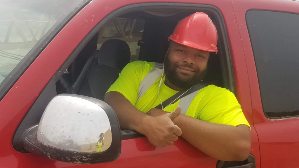 Man wearing a hardhat and giving a thumbs-up.